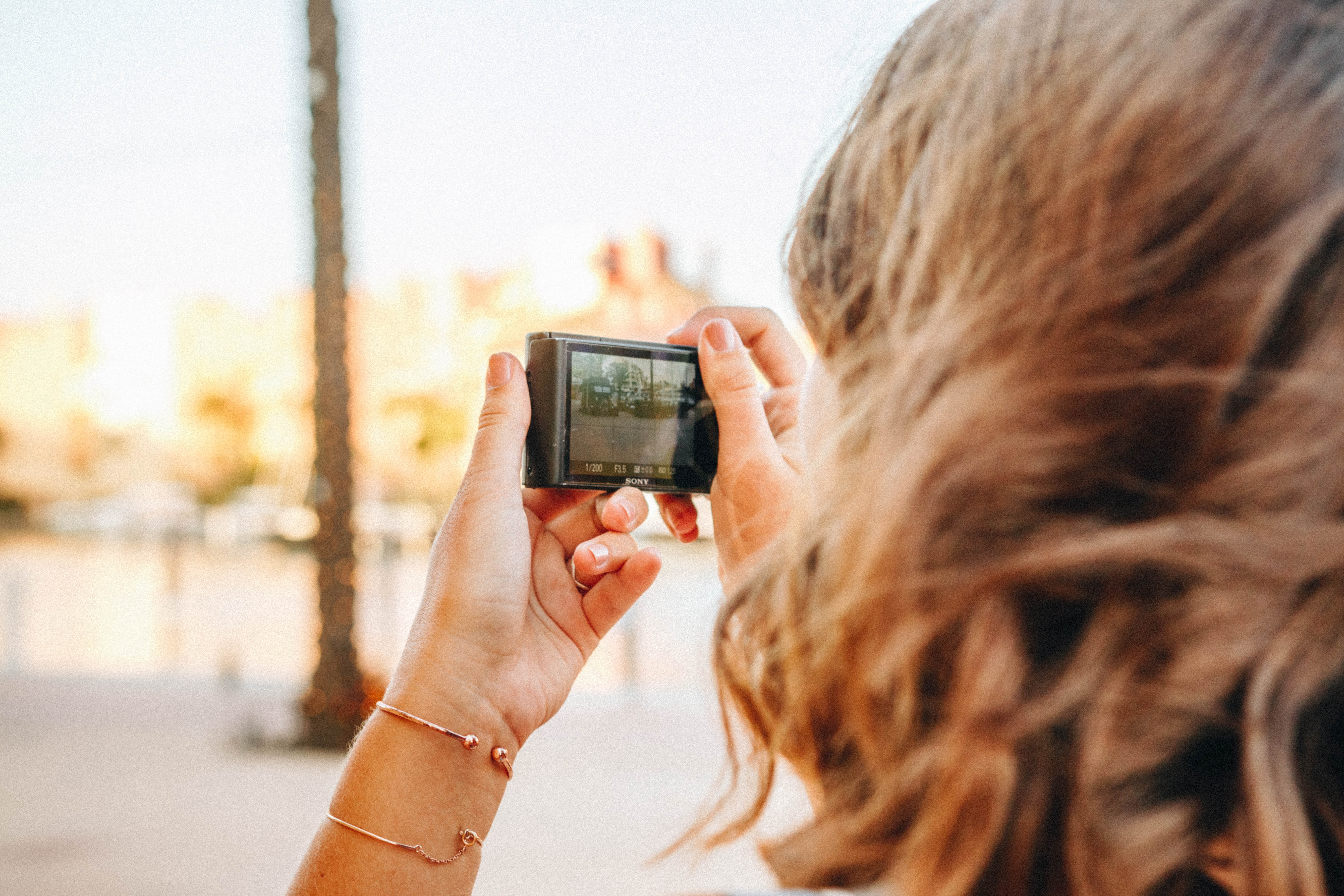 a woman using one of the best point and shoot camera under 300 dollars