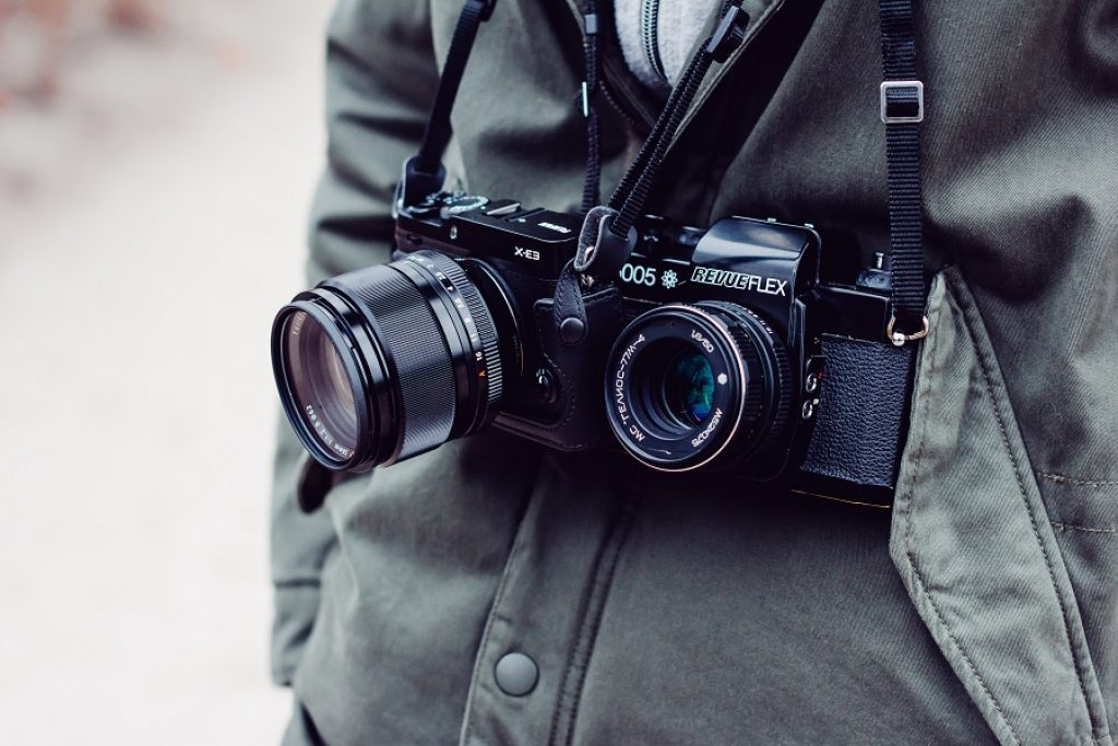 photo of a man with both dslr and point and shoot camera strapped around his neck