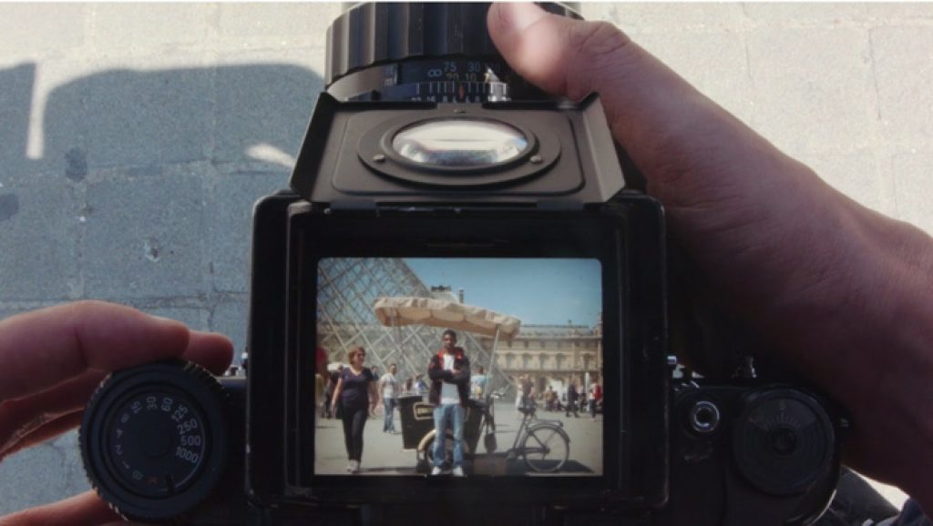 photo of a dslr camera with lcd screen on top