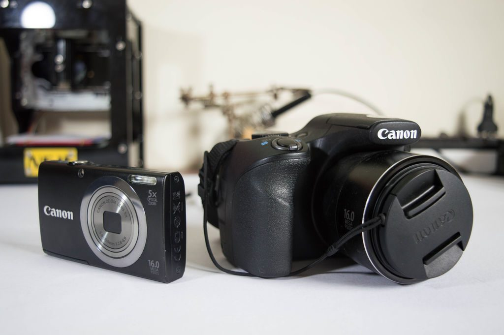 close-up photos of DSLR camera, on the right ,and the of the point and shoot camera, on the left