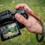 a man holding a camera and wearing green wrist strap, one of the best camera straps to buy
