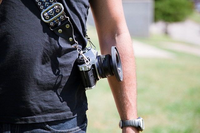 a man carrying a dslr camera using one of the best camera straps