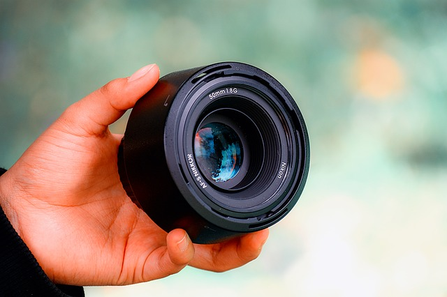 a man holding camera lens, one of the most important parts of a camera