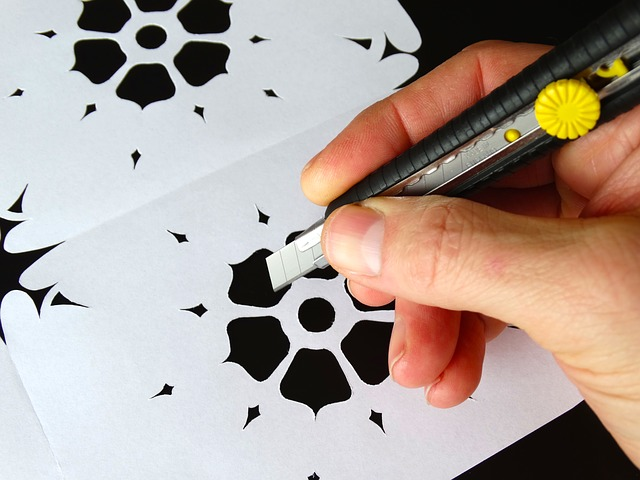 a person holding a cutter to smoothen the shape of die cut flower pattern produced by a die cutting machine