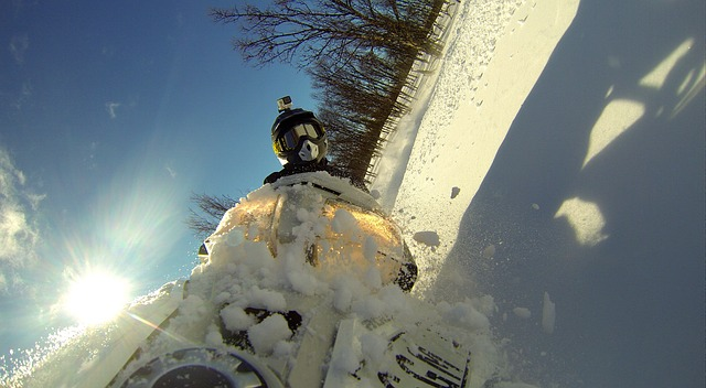 a man riding a snowmobile while wearing a helmet with gopro
